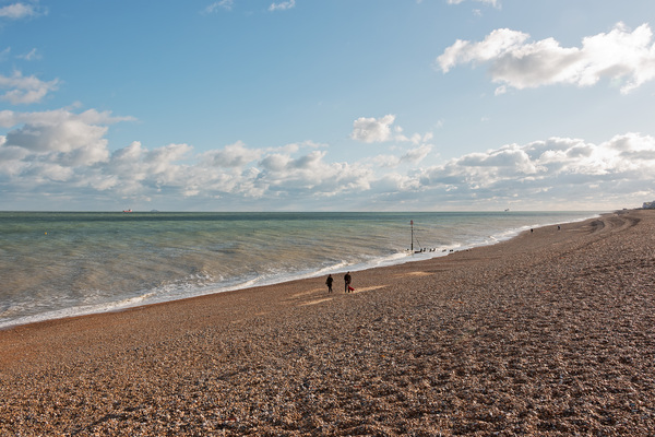Walking by the sea: Walkers on a shingle beach near Deal, Kent, England, in November.