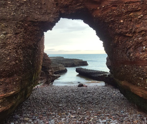 Sea arch: A natural arch formed at the base of sea cliffs, north of Arbroath, Scotland
