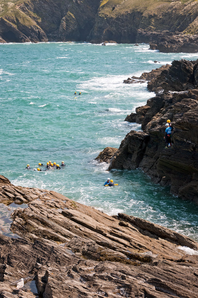 Coasteering: A group participating in the new sport of coasteering (climbing, abseiling and swimming) at coastal cliffs in Cornwall, England.