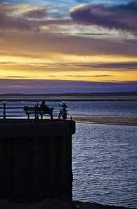 Solitude at sunset: a lone cyclist contemplates life as the sun sets over morecambe bay