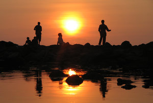 Unwind: Fisher folk relaxing at sunset.