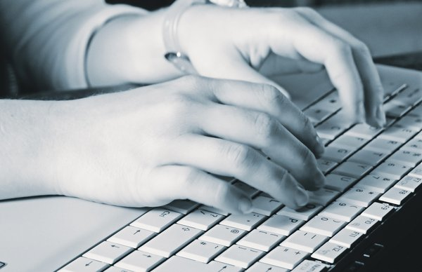 Hands typing: female hand on a keyboard