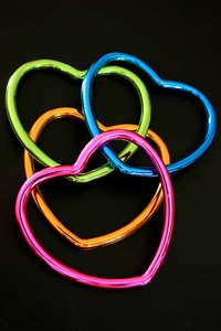 Entwined Hearts: Different coloured metal hearts against a black background