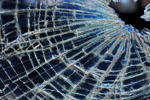Broken Window: Broken window of an old car in a junkyard.