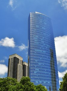 Skyscraper: Skyscraper with trees in front and blue sky in the background