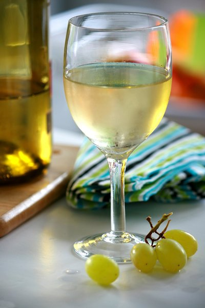 White Wine & Grapes: A glass of white wine with green grapes