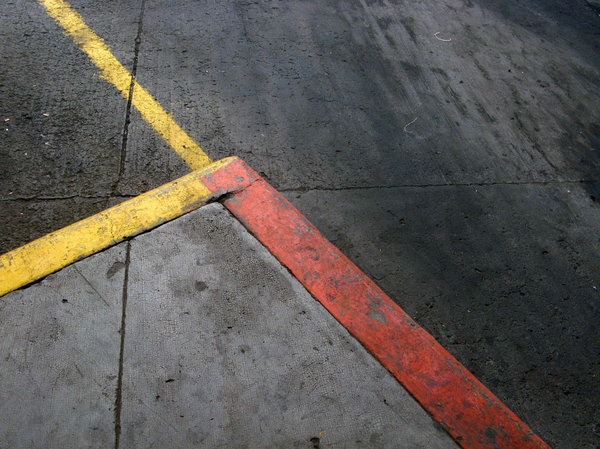 Concrete floor texture with co: Yellow and red colored lines in bus station parking spot