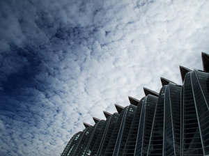 Glass jungle: Winter clouds over a ultra modern building, Corporations will swallow us all.