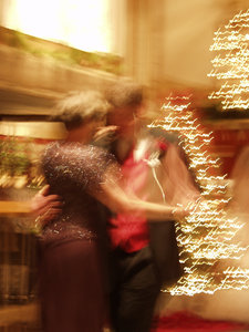 Waltz: Two motion blurred pictures of a couple dancing in formal attire with Christmas trees in the background.