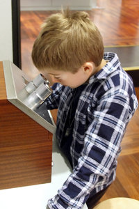 Young scientist: 7 year old boy by old microscope