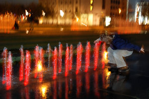 Night play with the light, wat: Boy playing with the water coloured by light