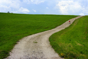 The long road: A young boy pushes his bike up a long country road.