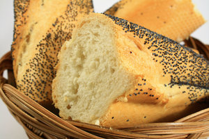Bread in Basket: Cut loaf of bread in a basket