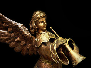 Angel: a heralding angel...Made of metal, the wings are a bit odd.  Photo not extracted, Background has been darkened and blurred.