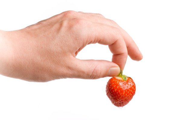 The Strawberry: Hand holding a fresh and wet strawberry