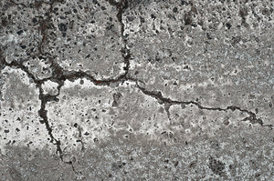 Cracked Pavement: Broken or cracked pavement at a crosswalk in Denver, Colorado.