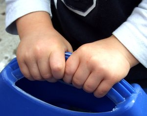 good grip: child's hands holding plastic container