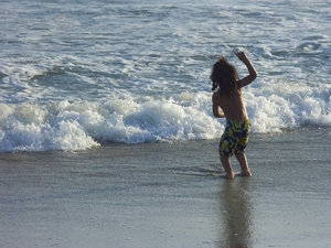 Child playing in the waves