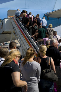 Flight_1: People walking up the stairs to an airplane
