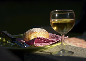Piece of bread: Piece of baked bread with a blurred glass of white wine