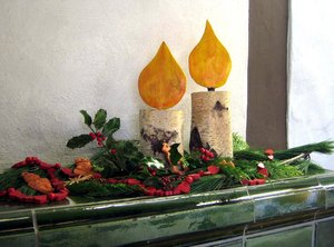 candles: wooden candles with christmas decoration on a tile stove