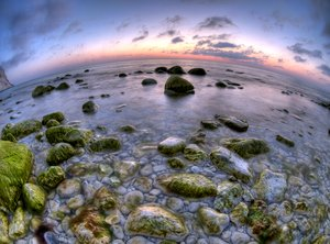 First light - HDR: The light before sunrise showing chalkrocks in the ocean, the pale morning sky and a chalkcliff. The picture is HDR using a fisheye lens.