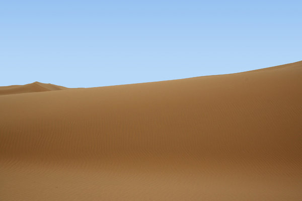 Desert dune: A large sand dune in the Tengger Desert, China. (Sky replaced with blue gradient.)