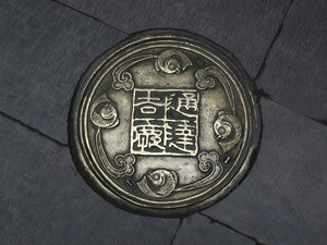 Manhole cover: An old manhole cover in a street in Tianjin, China.