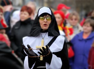 Nun: Nun, sister of mercy on parade, followed by crowd