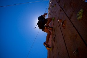 Rock Wall Climbing: 7 year old girl climbing a rock wall, silhouetted by the sun