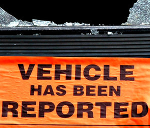 you've been notified: sign on stolen dumped and damaged motor car on roadside