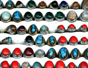 rows of rings: rows of brightly coloured signet rings with stones