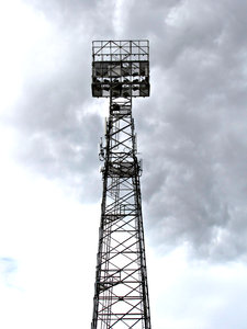 light tower - darkening sky: sports arena lighting tower with gathering storm clouds
