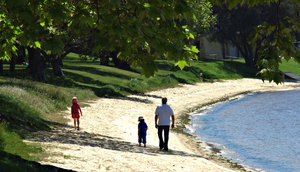 riverside stroll: father taking his chldren for a walk alongside the river