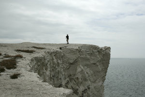 Don't step back!: A tourist taking a risk standing on a crumbling chalk cliff in East Sussex, England.