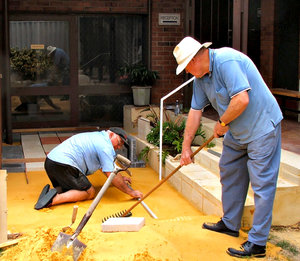 paving job: volunteer workers preparing sand for paving slabs
