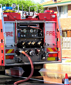fire & rescue action: fire and rescue team and vehicles attending suburban house fire