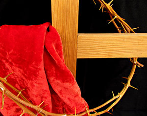 cross & crown of thorns: red cloth draped wooden cross and black background with crown of thorns