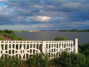 Fence by the danube: white fence by the danube in south ukraine under a dramatic cloudy sky. reni harbour visible in the background, romania on the opposite bank of the river.