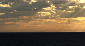 dark ocean skies: stormy skies over darkened Southern ocean with brilliant setting sun