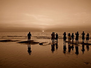 sepia sunset silhouettes: reflections of tourist photographers snapping the sunset