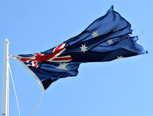 loose and tattered: a tattered loosely tied Australian flag flapping in the wind