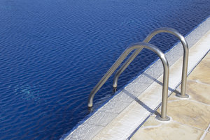Swimming pool handrail: Handrail and steps into a large outdoor swimming pool.