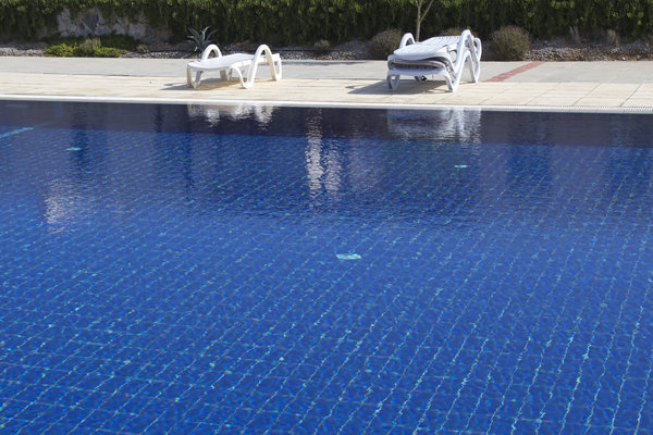Swimming pool and loungers: Loungers by a large outdoor swimming pool.