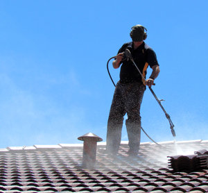 roof restoration3: workman cleaning roof tiles for restoration