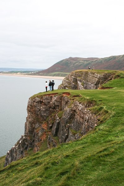 Clifftop tourists: Tourists admiring the view from a clifftop on the Gower, Wales.