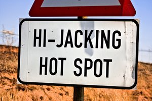 Hi-Jacking Hotspot Sign: Close-up of a highway road sign reading HI-JACKING HOTSPOT located near Witbank, South Africa. A little roughly captured, but I didn't exactly want to stick around too long for reasons apparent on the sign.