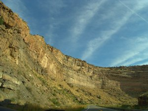 Highway to Grand Mesa,Colorado: High cliff walls aline the highway to Grand Mesa, Colorado and is a stricking road trip with blue sky above.