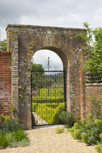 Garden gate: An ornamental gate to a box hedge garden in West Sussex, England.