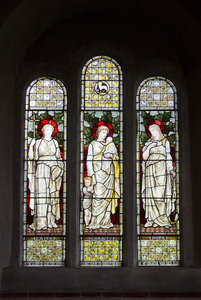 Church window: A stained glass window depicting faith, hope and charity in an old church in England.